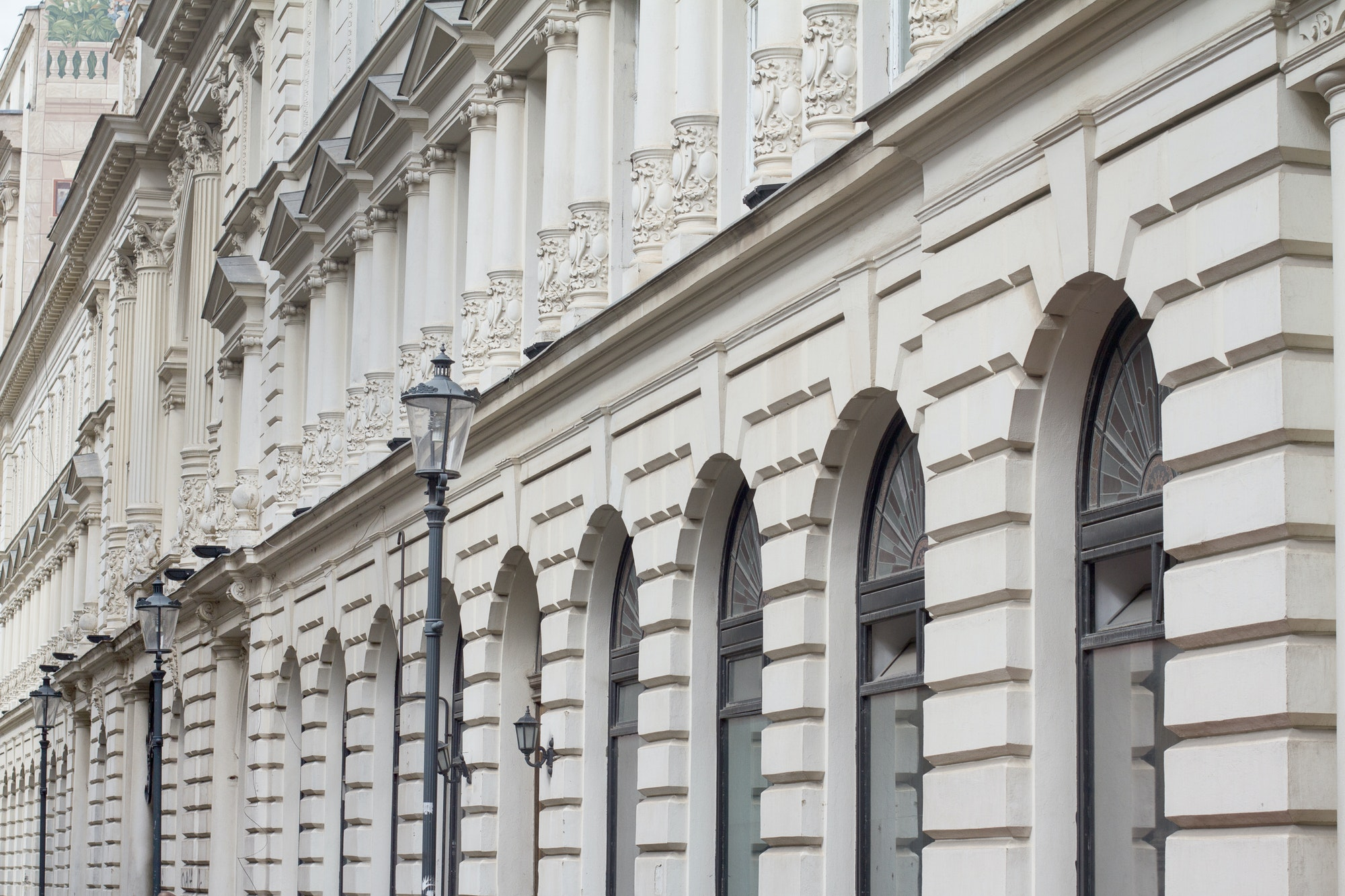 White, classical building architecture with windows and street l
